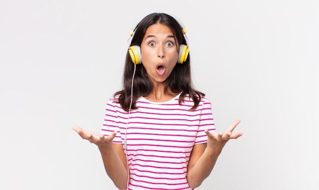 Junge hispanische frau, die extrem schockiert und überrascht ist, musik mit kopfhörern zu hören