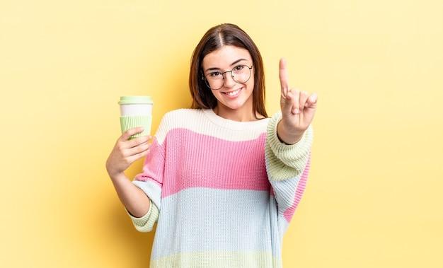 Junge hispanische frau, die freundlich lächelt und aussieht und nummer eins zeigt. kaffee zum mitnehmen konzept