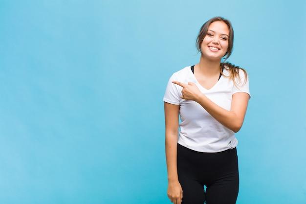 Junge hispanische frau, die fröhlich lächelt, glücklich fühlt und zur seite zeigt