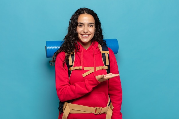 Junge hispanische frau, die fröhlich lächelt, sich glücklich fühlt und ein konzept im kopienraum mit handfläche zeigt