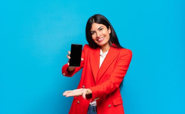 Junge hispanische frau, die fröhlich lächelt, sich glücklich fühlt und ein konzept im kopierraum mit handfläche zeigt. kopierplatz auf dem telefonbildschirm