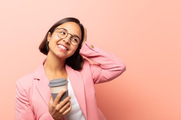 Junge hispanische frau, die fröhlich und lässig lächelt und die hand mit einem positiven, glücklichen und selbstbewussten blick an den kopf nimmt