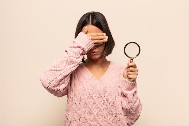 Junge hispanische frau, die gesicht mit beiden händen bedeckt, die nein sagen! bilder ablehnen oder fotos verbieten