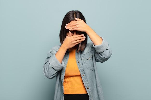 Junge hispanische frau, die gesicht mit beiden händen bedeckt und nein sagt! bilder ablehnen oder fotos verbieten