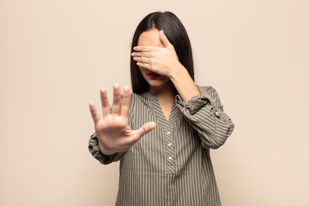 Junge hispanische frau, die gesicht mit hand bedeckt und andere hand nach vorne legt, um kamera zu stoppen, fotos oder bilder ablehnend