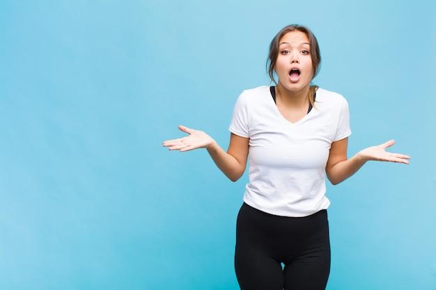 Junge hispanische frau, die glücklich, aufgeregt, überrascht oder schockiert fühlt