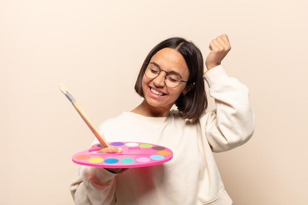 Junge hispanische frau, die glücklich, erstaunt und überrascht aussieht, lächelt und erstaunliche und unglaublich gute nachrichten realisiert