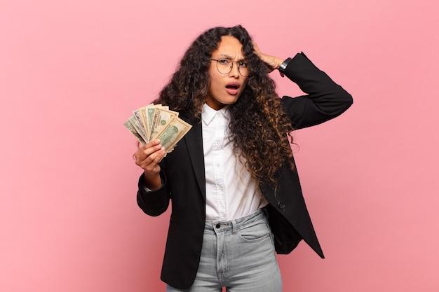 Junge hispanische frau, die glücklich, erstaunt und überrascht aussieht, lächelt und erstaunliche und unglaubliche gute nachrichten erkennt. dollar-banknoten-konzept