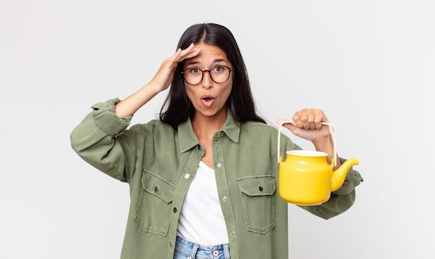 Junge hispanische frau, die glücklich, erstaunt und überrascht aussieht und eine teekanne hält Premium Fotos