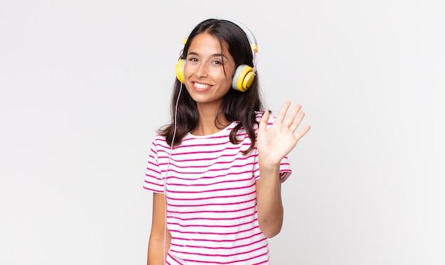 Junge hispanische frau, die glücklich lächelt, die hand winkt, sie begrüßt und begrüßt, wenn sie musik mit kopfhörern hören