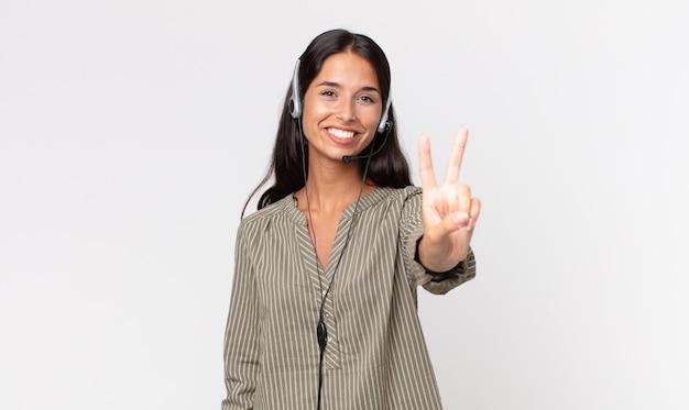 Junge hispanische frau, die glücklich lächelt und schaut und sieg oder frieden mit einem kopfhörer gestikuliert. telefonmarketing-konzept