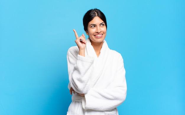 Junge hispanische frau, die glücklich lächelt und seitwärts schaut, sich wundert, denkt oder eine idee hat. bademantel-konzept