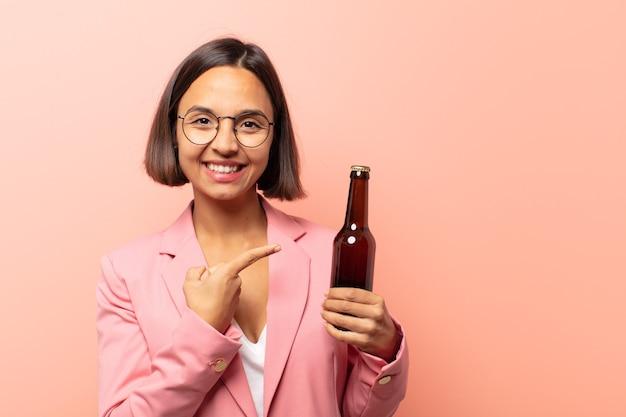 Junge hispanische frau, die glücklich lächelt und zur seite und nach oben zeigt, wobei beide hände objekt im kopienraum zeigen