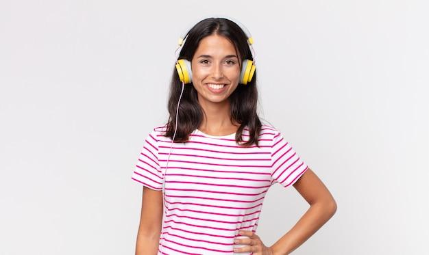 Junge hispanische frau, die glücklich mit einer hand auf der hüfte lächelt und selbstbewusst musik mit kopfhörern hört
