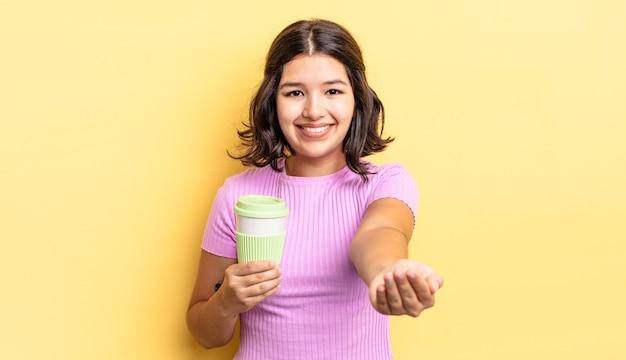 Junge hispanische frau, die glücklich mit freundlichem lächeln lächelt und ein konzept anbietet und zeigt. kaffee zum mitnehmen konzept