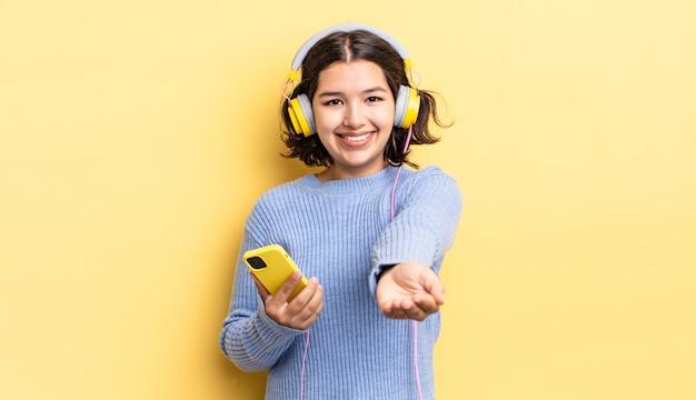 Junge hispanische frau, die glücklich mit freundlichem lächeln lächelt und ein konzept anbietet und zeigt. kopfhörer- und smartphone-konzept