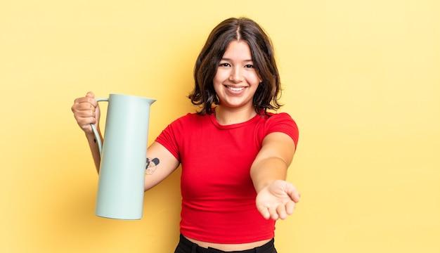 Junge hispanische frau, die glücklich mit freundlichem lächeln lächelt und ein konzept anbietet und zeigt. thermos-konzept