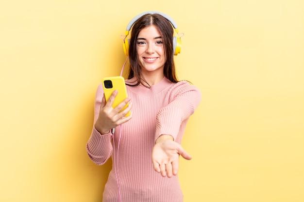Junge hispanische frau, die glücklich mit freundlichem lächelt und ein konzept anbietet und zeigt. kopfhörer- und telefonkonzept