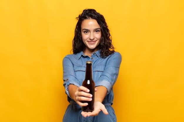 Junge hispanische frau, die glücklich mit freundlichem, selbstbewusstem, positivem blick lächelt und ein objekt oder konzept anbietet und zeigt