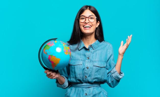 Junge hispanische frau, die glücklich, überrascht und fröhlich fühlt, mit positiver einstellung lächelt und eine lösung oder idee verwirklicht. erdplanetenkonzept