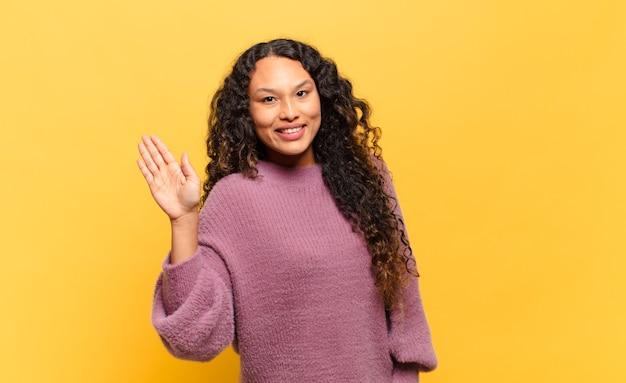 Junge hispanische frau, die glücklich und fröhlich lächelt, die hand winkt, sie begrüßt und begrüßt oder sich verabschiedet
