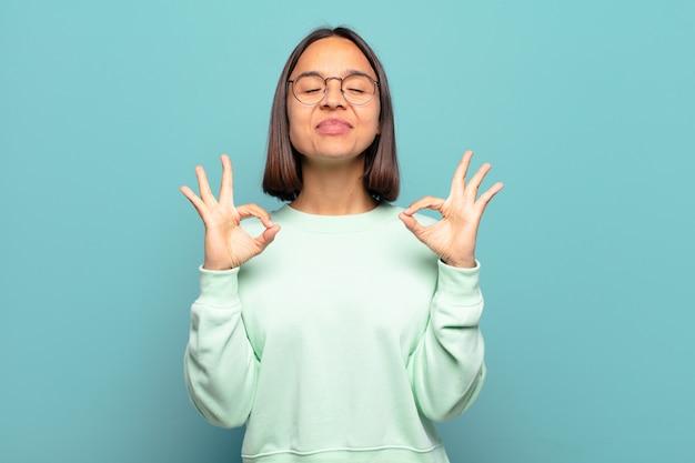Junge hispanische frau, die konzentriert und meditierend aussieht, sich zufrieden und entspannt fühlt, denkt oder eine wahl trifft