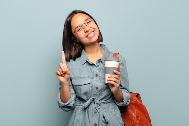 Junge hispanische frau, die lächelt und freundlich aussieht, die nummer eins oder zuerst mit der hand nach vorne zeigt, herunterzählt