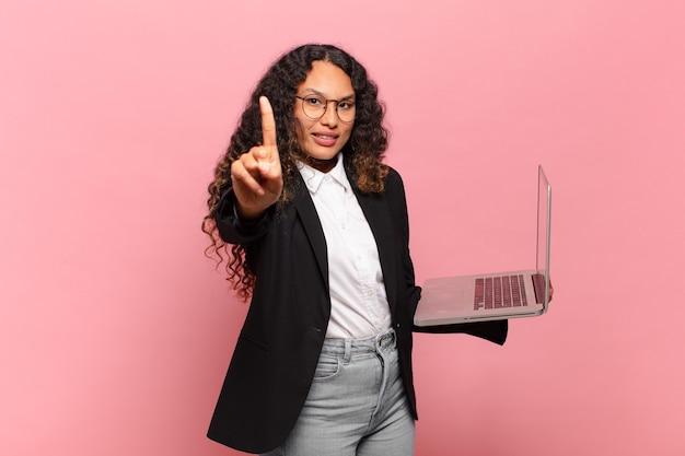 Junge hispanische frau, die lächelt und freundlich aussieht, die nummer eins oder zuerst mit der hand nach vorne zeigt und herunterzählt. laptop-konzept