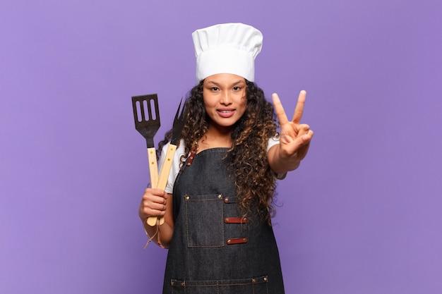 Junge hispanische frau, die lächelt und freundlich aussieht, die nummer zwei oder die zweite mit der hand nach vorne zeigt und herunterzählt. barbecue-koch-konzept