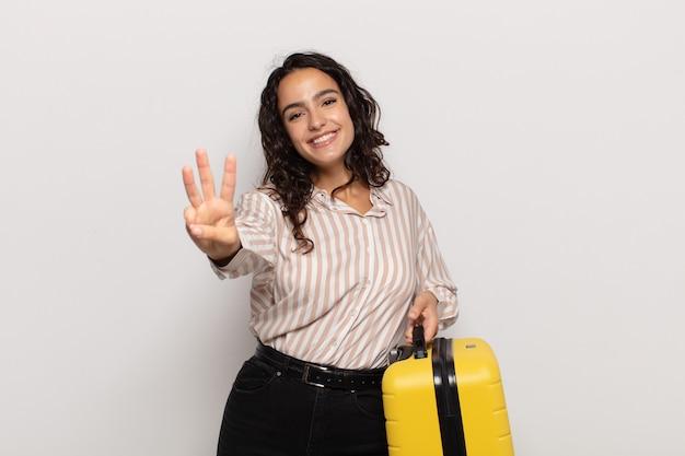Junge hispanische frau, die lächelt und freundlich aussieht, nummer drei oder dritte mit der hand nach vorne zeigend, countdown