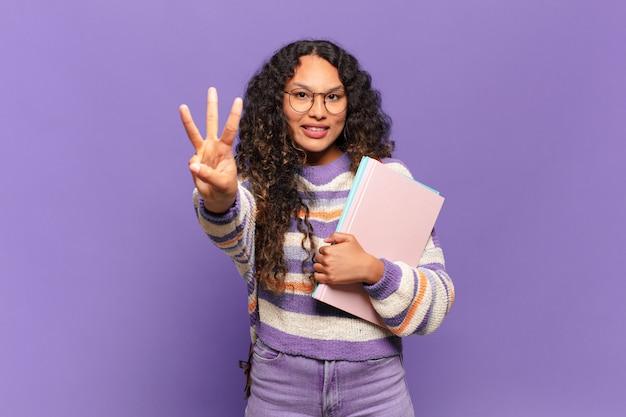 Junge hispanische frau, die lächelt und freundlich aussieht, nummer drei oder dritte mit der hand nach vorne zeigt, herunterzählen. studentisches konzept