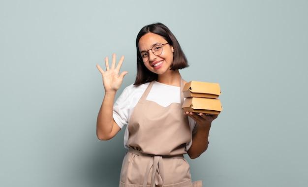 Junge hispanische frau, die lächelt und freundlich aussieht, nummer fünf oder fünften mit der hand nach vorne zeigend, herunterzählend