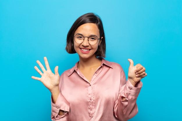 Junge hispanische frau, die lächelt und freundlich aussieht, nummer sechs oder sechste mit der hand nach vorne zeigend, countdown