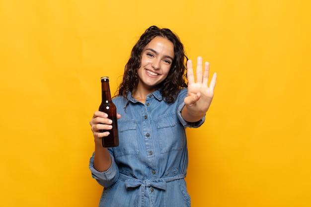 Junge hispanische frau, die lächelt und freundlich aussieht, nummer vier oder vierten mit der hand nach vorne zeigend, countdown