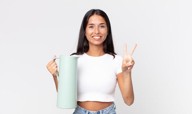 Junge hispanische frau, die lächelt und freundlich aussieht, nummer zwei zeigt und eine kaffeethermos hält