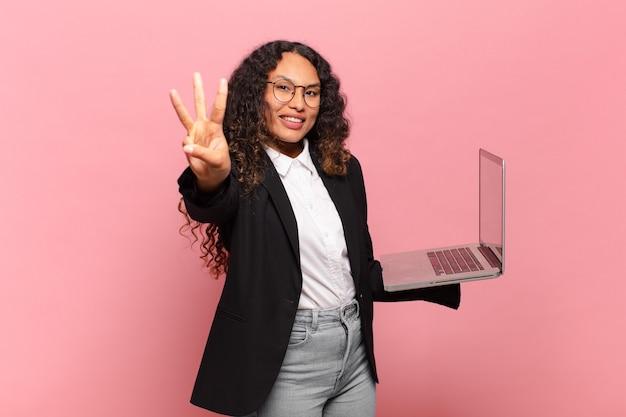 Junge hispanische frau, die lächelt und freundlich aussieht und nummer drei oder dritte mit der hand nach vorne zeigt, herunterzählen. laptop-konzept