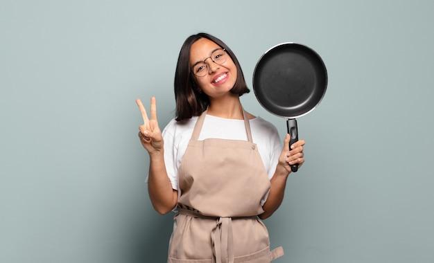 Junge hispanische frau, die lächelt und glücklich, sorglos und positiv aussieht, sieg oder frieden mit einer hand gestikulierend