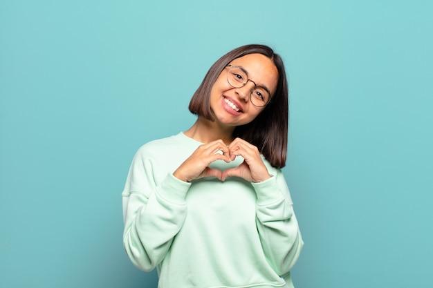 Junge hispanische frau, die lächelt und sich glücklich, süß, romantisch und verliebt fühlt und herzform mit beiden händen bildet