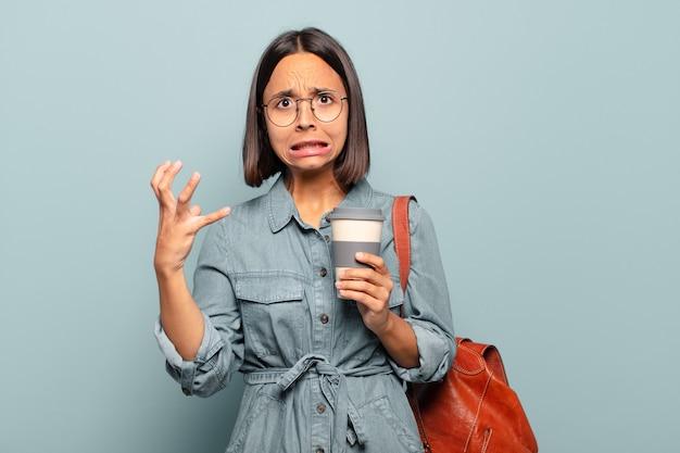 Junge hispanische frau, die mit den händen in der luft schreit und sich wütend, frustriert, gestresst und verärgert fühlt