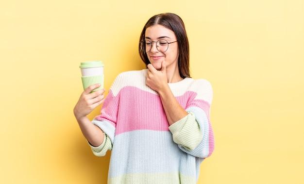 Junge hispanische frau, die mit einem glücklichen, selbstbewussten ausdruck mit der hand am kinn lächelt. kaffee zum mitnehmen konzept