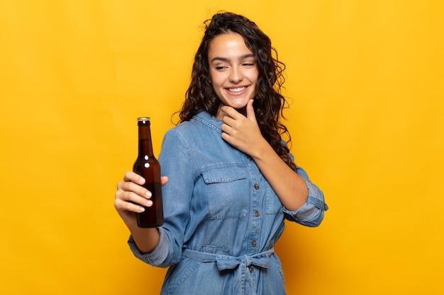 Junge hispanische frau, die mit einem glücklichen, selbstbewussten ausdruck mit der hand am kinn lächelt, sich wundert und zur seite schaut