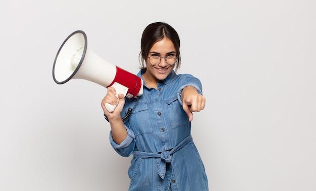 Junge hispanische frau, die mit einem zufriedenen, selbstbewussten, freundlichen lächeln nach vorne zeigt und sie wählt