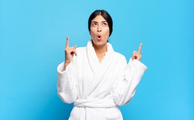 Junge hispanische frau, die schockiert, erstaunt und mit offenem mund aussieht und mit beiden händen nach oben zeigt, um den raum zu kopieren. bademantel-konzept