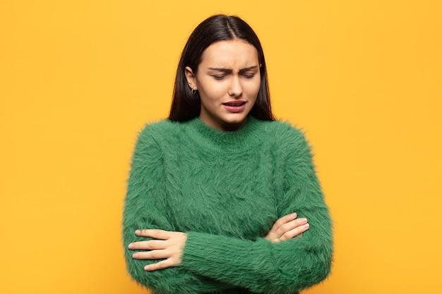 Junge hispanische frau, die sich ängstlich, krank, krank und unglücklich fühlt und unter schmerzhaften bauchschmerzen oder grippe leidet