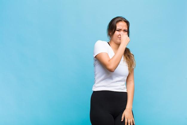 Junge hispanische frau, die sich angewidert fühlt und die nase hält, um einen üblen und unangenehmen gestank zu vermeiden