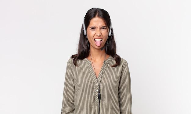 Junge hispanische frau, die sich angewidert und gereizt fühlt und mit einem headset die zunge herausstreckt. telefonmarketing-konzept