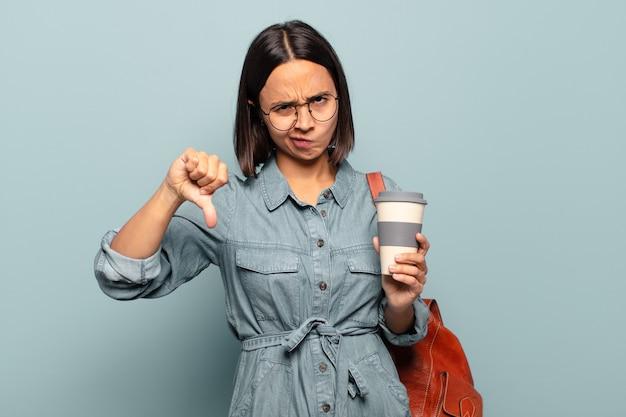 Junge hispanische frau, die sich böse, wütend, verärgert, enttäuscht oder unzufrieden fühlt und mit einem ernsten blick die daumen nach unten zeigt