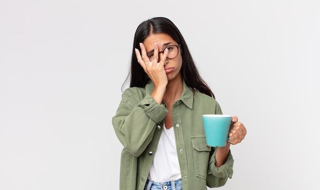 Junge hispanische frau, die sich gelangweilt, frustriert und schläfrig fühlt, nachdem sie ermüdend war und eine kaffeetasse hielt