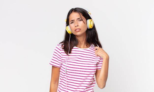 Junge hispanische frau, die sich gestresst, ängstlich, müde und frustriert fühlt, musik mit kopfhörern zu hören