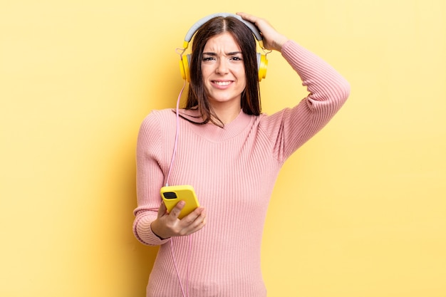 Junge hispanische frau, die sich gestresst, ängstlich oder ängstlich fühlt, mit den händen auf dem kopf. kopfhörer- und telefonkonzept